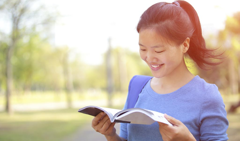 teen girl with adhd flipping through college brochure and smiling outside