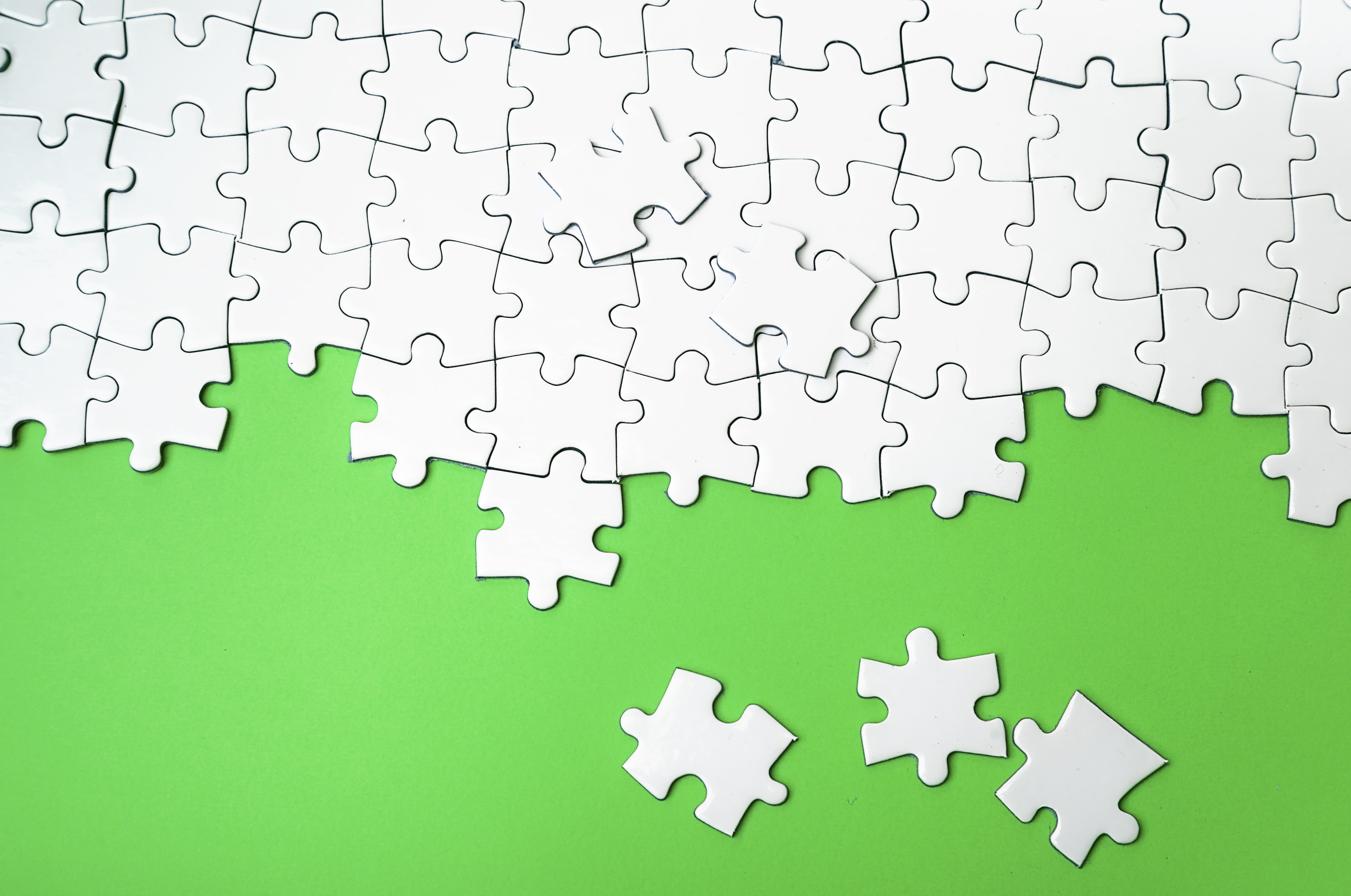 White puzzle pieces on a green background, a metaphor for leaving projects  incomplete when ADHD