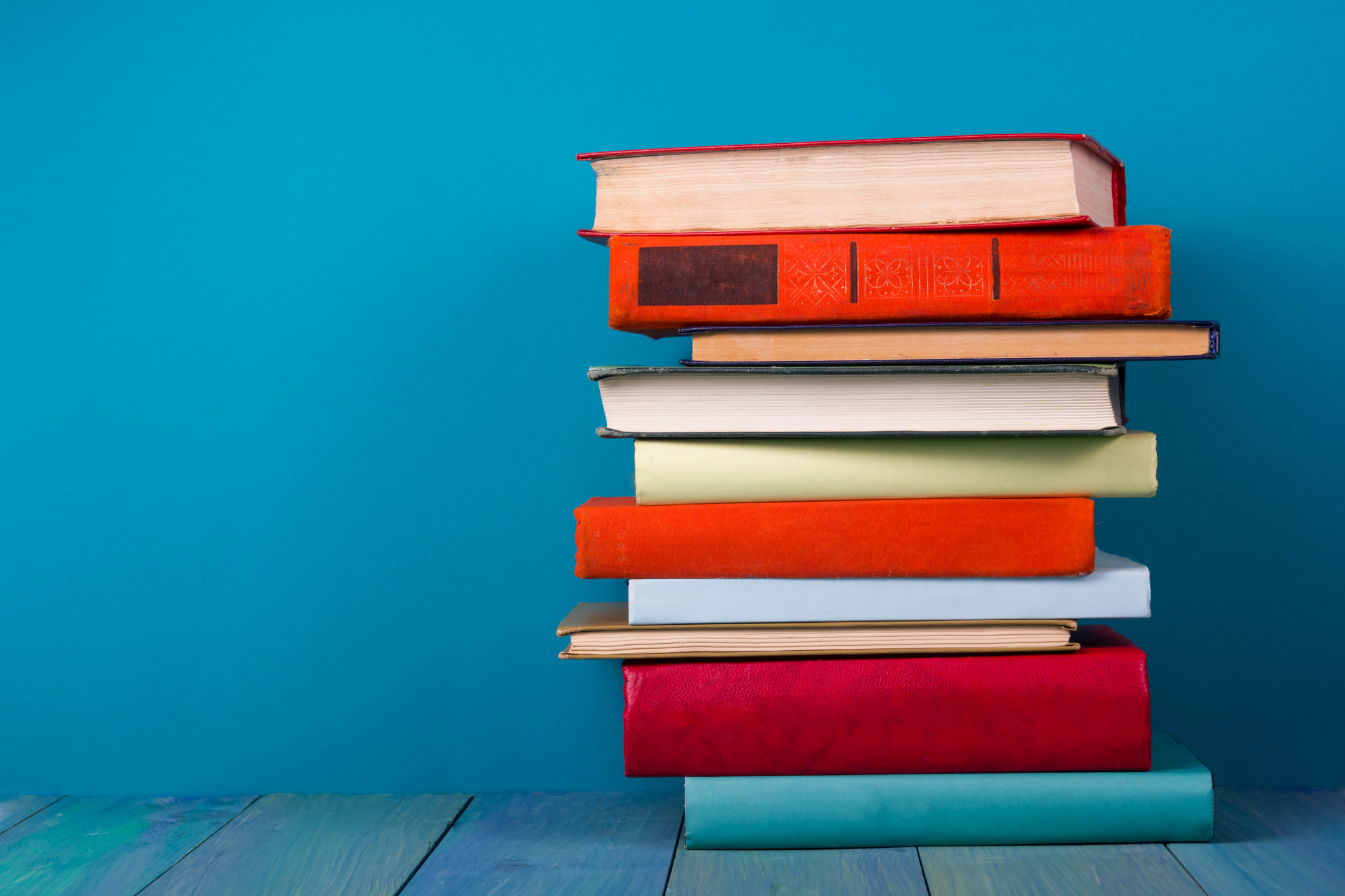 Stack of colorful books, grungy blue background, free copy space ...