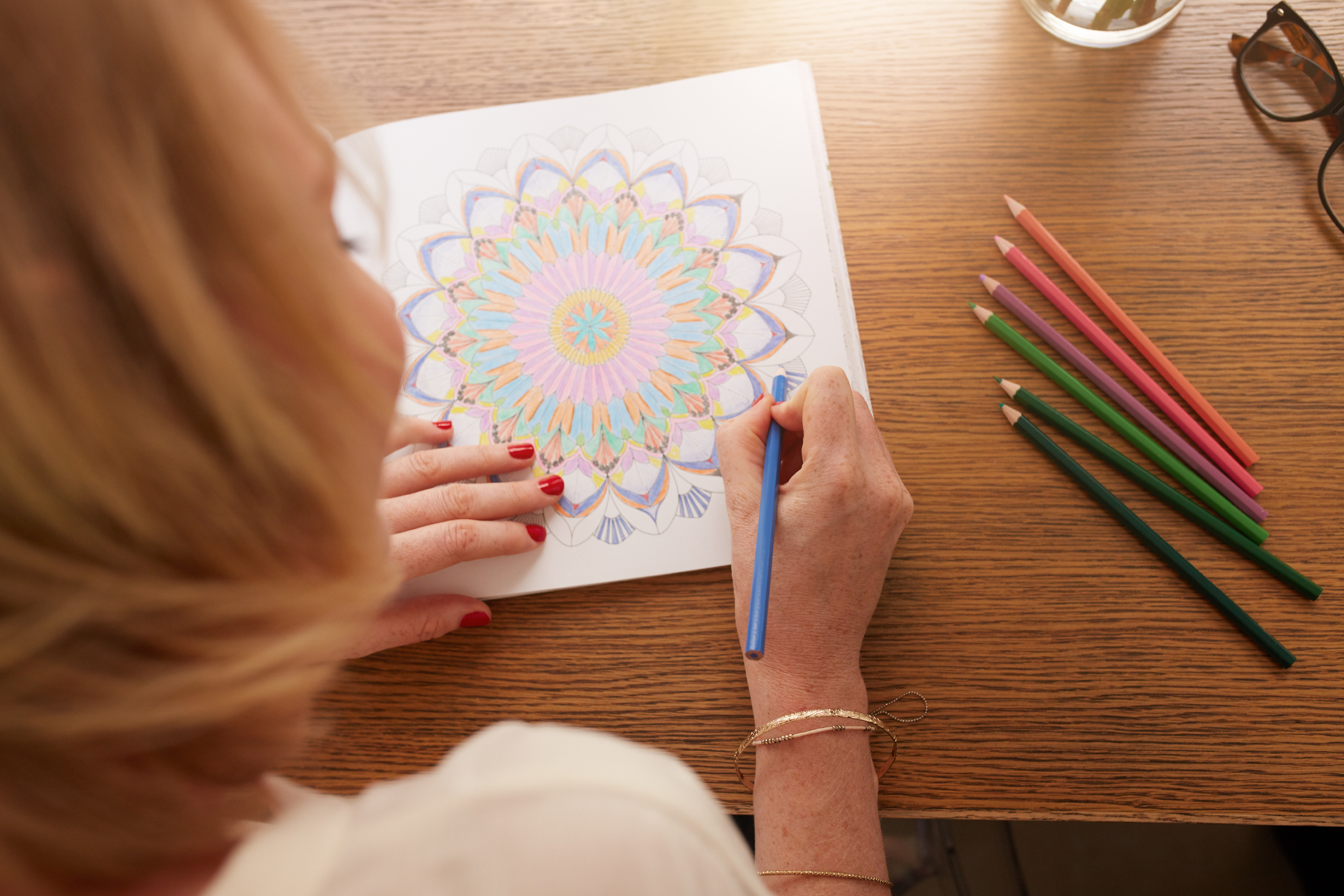 Overhead View Of ADHD Woman Drawing In Adult Coloring Book With Color Pencils For Anti